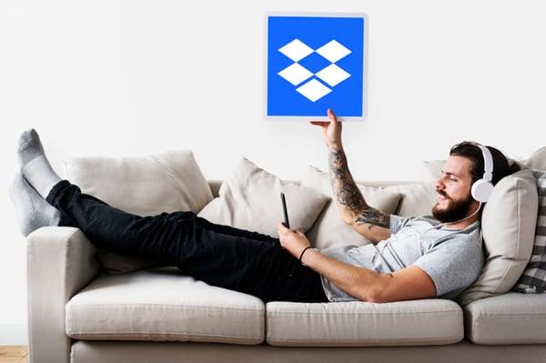 hombre-mostrando-icono-dropbox-sofa_53876-65419